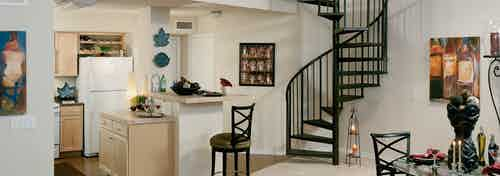 Interior view of townhome kitchen and dining room at AMLI Memorial Heights apartments with stairs leading to upstairs loft