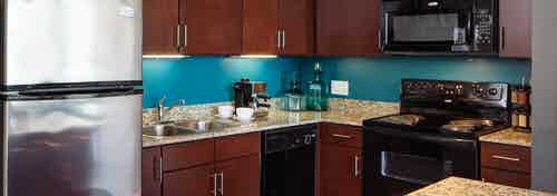 An interior view of an AMLI 900 kitchen which has teal painted walls and features dark wood cabinets and granite countertops