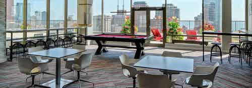 Rooftop lounge at AMLI 900 featuring tables, chairs and a pool table surrounded by glass windows with a daytime city view