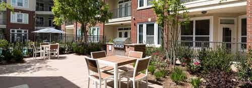 Daytime view of grill station at AMLI Frisco Crossing apartments with seating and surrounding trees, shrubs and flowers