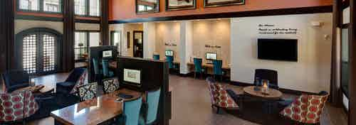 Interior of leasing office at AMLI at Escena apartment building with seating area, desks with chairs and computer stations