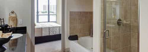 Interior of AMLI Las Colinas apartment bathroom with black granite double vanity and glass shower and oval garden tub