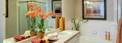 Interior of bathroom at AMLI Memorial Heights with double vanity with white cabinets and oval garden tub with tile surround