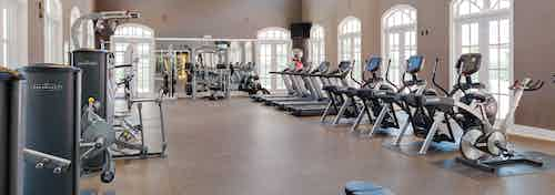 Interior view of fitness center at AMLI Memorial Heights apartments with strength and cardio machines and many windows