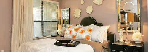 Interior view of AMLI at Escena apartment bedroom with bed and nightstand and large window with blinds and curtain