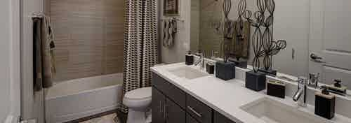 Interior view of bathroom at AMLI Lofts containing a double vanity, toilet and bathtub with a striped curtain and beige tiles