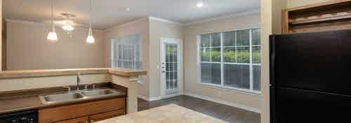 Interior view from island kitchen into living and dining rooms with large windows at AMLI Memorial Heights apartments