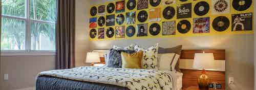 Interior view of an AMLI Sawgrass Village apartment bedroom with a bed underneath wall art made from vinyl record albums