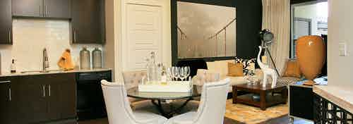 Interior of AMLI at Escena apartment kitchen with tile backsplash, dining area with table and chairs and living room