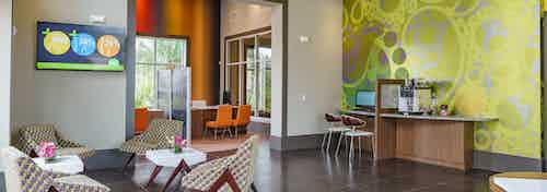 The leasing office at AMLI Sawgrass Village with high ceilings, seating and a coffee bar near an ornate wall mural