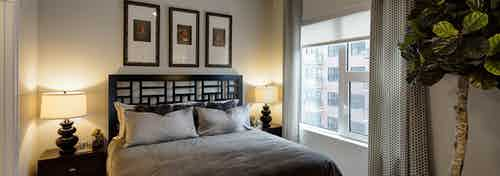 Bedroom at AMLI Lofts with creme colored walls and black and gray furnishings with a bright window view overlooking the city