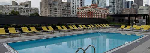 The pool at AMLI Lofts in the daylight with yellow chairs aligning the surrounding pavement and the city skyline in the back