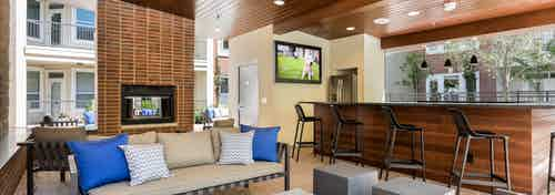 Daytime view of cabana at AMLI Frisco Crossing apartments with serving bar and big screen TV and seating and fireplace