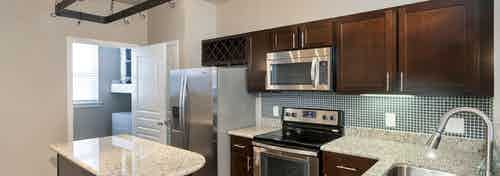 AMLI Memorial Heights apartment kitchen with dark wood cabinets, stainless steel appliances and granite island and counters