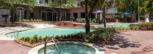 Heated spa, swimming pool and clubhouse with landscaping and trees at AMLI Memorial Heights apartment building