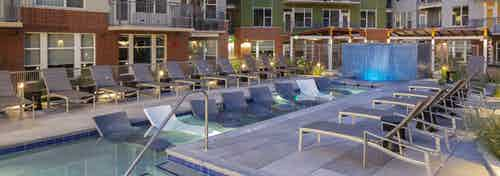 Nighttime view of the pool at AMLI Riverfront green apartments with several lounge chairs and a tiled waterfall fountain