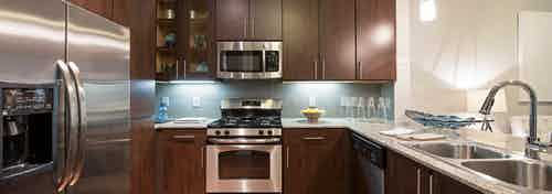 AMLI Uptown apartment kitchen with dark brown solid and glass shaker cabinets and tile backsplash and stainless appliances