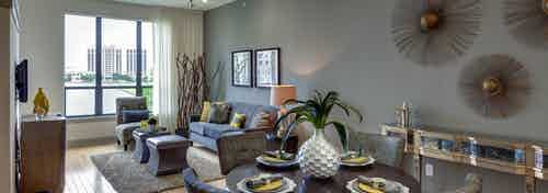 Interior view of AMLI Las Colinas apartment living and dining space with wood floors and large window overlooking lake