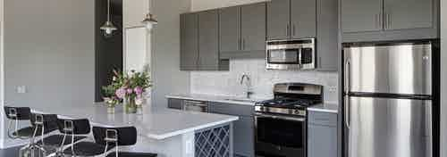 An AMLI Lofts kitchen which is painted gray and white and has an island with quartz countertops and four black bar stools