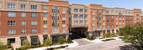 Daytime exterior view of AMLI River Oaks brick apartment building entrance with black awnings and tree-lined street