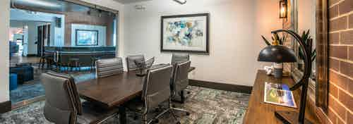Interior of conference room at AMLI Las Colinas apartment building with wood table and six chairs and artwork on walls