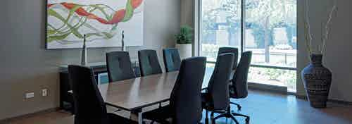 A modern styled conference room at AMLI 900 with a long wooden table and eight swivel chairs paired with tile flooring