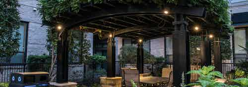 Nighttime view of verandah covered with greenery at AMLI Las Colinas apartment building with table and chairs and lights