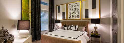 AMLI Uptown apartment bedroom with bed, two nightstands with lamps and dresser and window with blinds and curtains