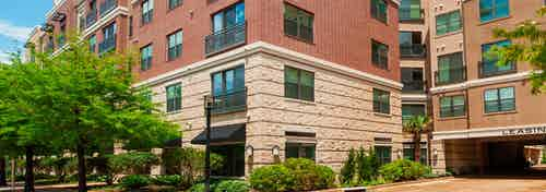 Daytime exterior view of AMLI Uptown brick apartment building and garage entrance and tree lined street with bushes