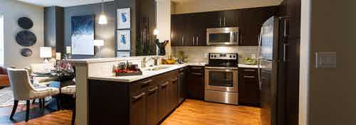 AMLI River Oaks apartment kitchen with stainless steel appliances, dark wood cabinetry, wood floors and dining table at left