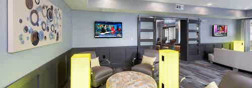 Clubroom at AMLI Piedmont Heights with multiple areas of seating next to large neon electrical ports to charge electronics