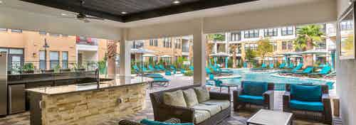 Daytime view of AMLI Campion Trail cabana with comfortable seating and serving bar overlooking pool area with lounges