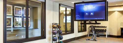 Interior of workout room at AMLI Campion Trail apartments with fitness on demand on big screen TV, dumbbells and balls
