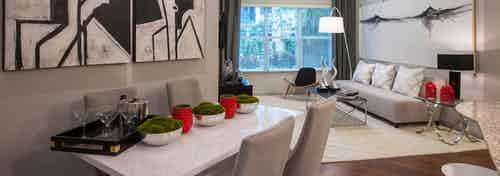 Interior view of dining room with white table and chairs looking into living room with large window at AMLI Uptown apartments