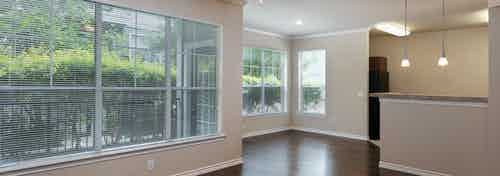 AMLI Memorial Heights apartment living and dining rooms with dark wood floors and large windows with blinds