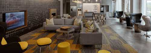 The resident clubroom at AMLI Lofts which has multiple seating areas and a large TV with vibrant yellow accents in the decor