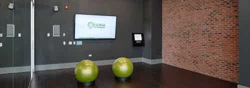 Studio with fitness on demand at AMLI Lofts with wide open space for exercise as well as a flat screen TV and exercise balls