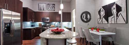 AMLI Uptown apartment island kitchen with granite countertops and stainless steel appliances and dark brown wood cabinetry