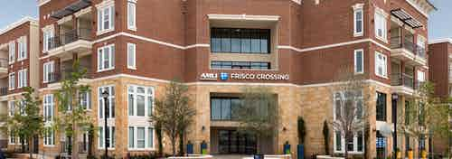 Daytime exterior view of AMLI Frisco Crossing apartment brick facade with sign above building entrance and trees