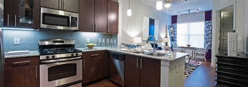 Interior view of AMLI Uptown apartment kitchen with dark brown cabinets and stainless steel appliances and living room
