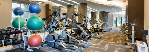 AMLI River Oaks fitness center with strength and cardio equipment's and dumbbells and colorful stability balls at left