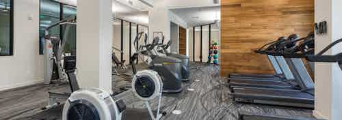Fitness center at AMLI Frisco Crossing apartments with treadmills and other cardio machines and wood wall and white pillars