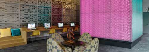 Interior view of the tech lounge at AMLI Lofts with a large pink cube that changes color serving as the focal point