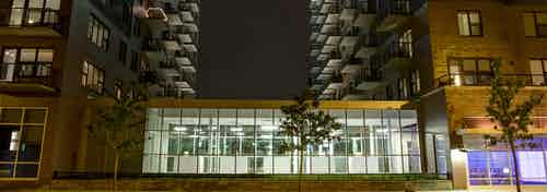 Exterior view of the AMLI Lofts apartment community building facade brightly lit up at night time in the city of Chicago