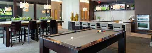 Interior view of resident lounge with billiards table, kitchen and various seating at AMLI River Oaks apartment building