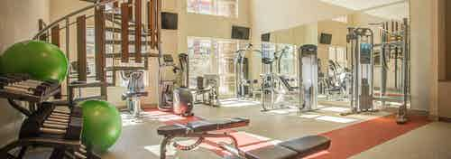View of fitness center at AMLI Interlocken apartments with free weights and other strength training machines and staircase
