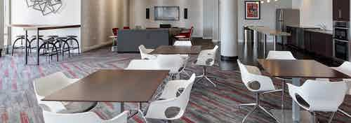 Rooftop lounge at AMLI 900 decorated in neutral colors with red accents, featuring various seating options and a kitchenette