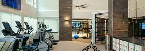 Fitness center at AMLI Riverfront Green apartments with multiple treadmills and elliptical machines with overhead fans