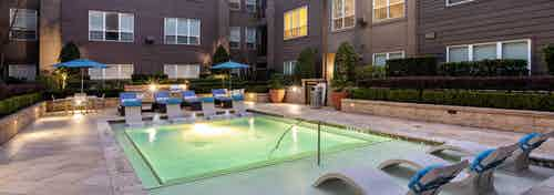 Nighttime view of AMLI River Oaks swimming pool with lounge seating and manicured shrubbery encircled by apartment building