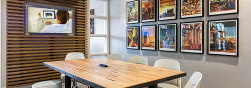 Interior view of conference room at AMLI Frisco Crossing apartment building with wood table, chairs and big screen TV